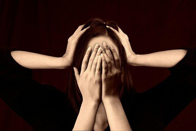 頭を抱え両手で顔を覆う女性