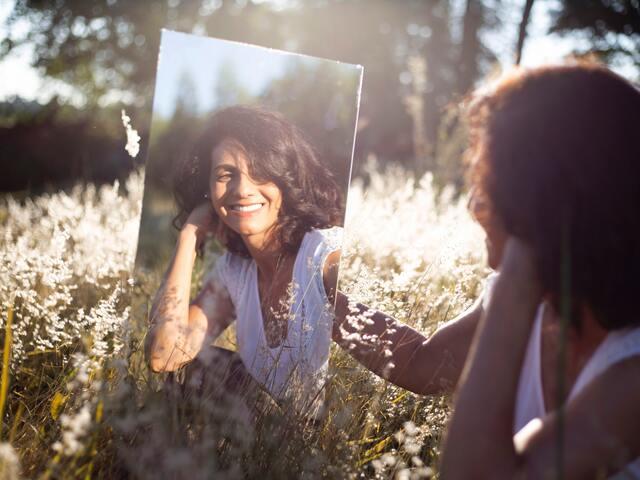 鏡に映った自分を見つめる女性