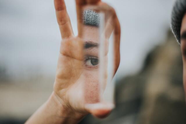 小さな鏡に顔の一部を映す女性